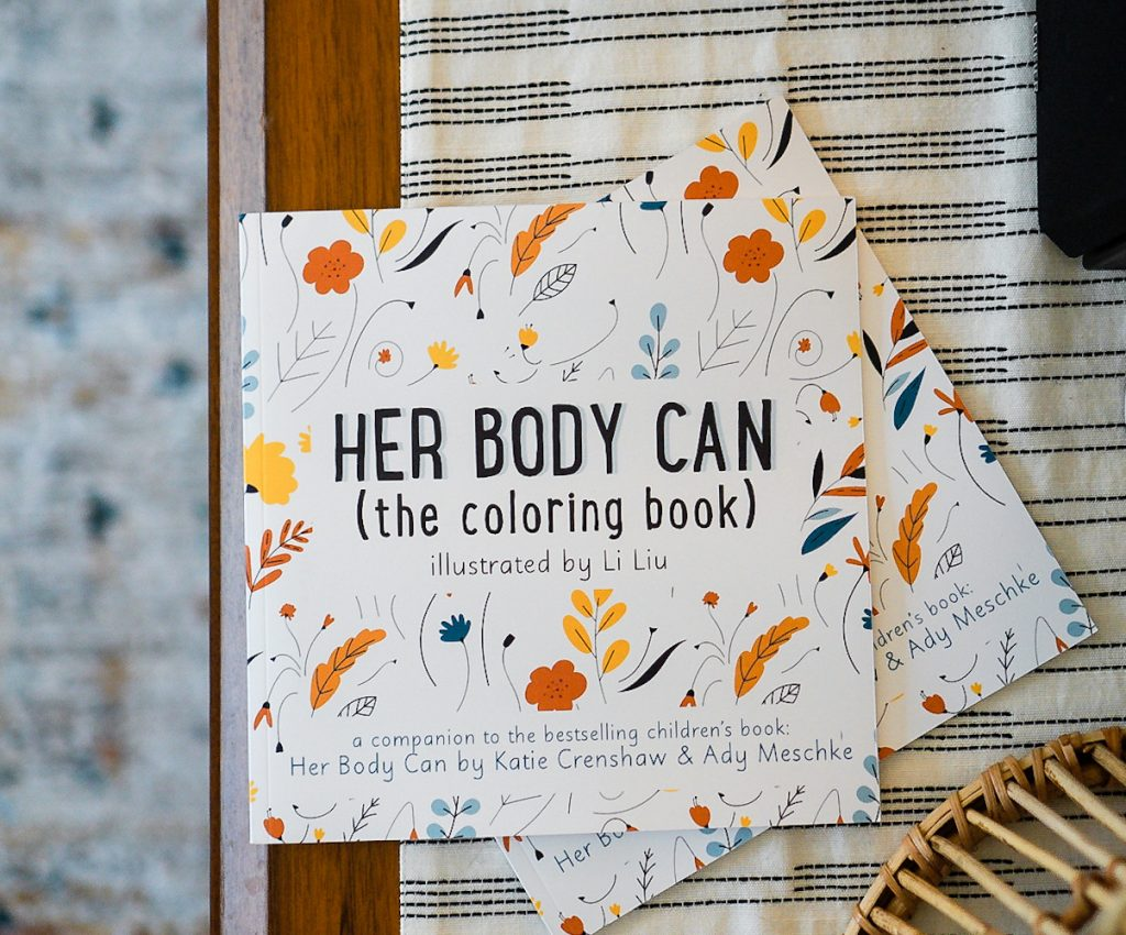 Two copies of Her Body Can (the coloring book), by Katie Crenshaw and Ady Meschke, sit on top of a pretty tablecloth on a table over a rug.