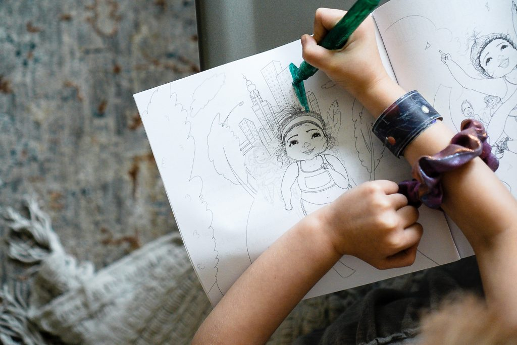 Katie Crenshaw's daughter colors a girl crossing the finish line of a marathon from Her Body Can (the coloring book).
