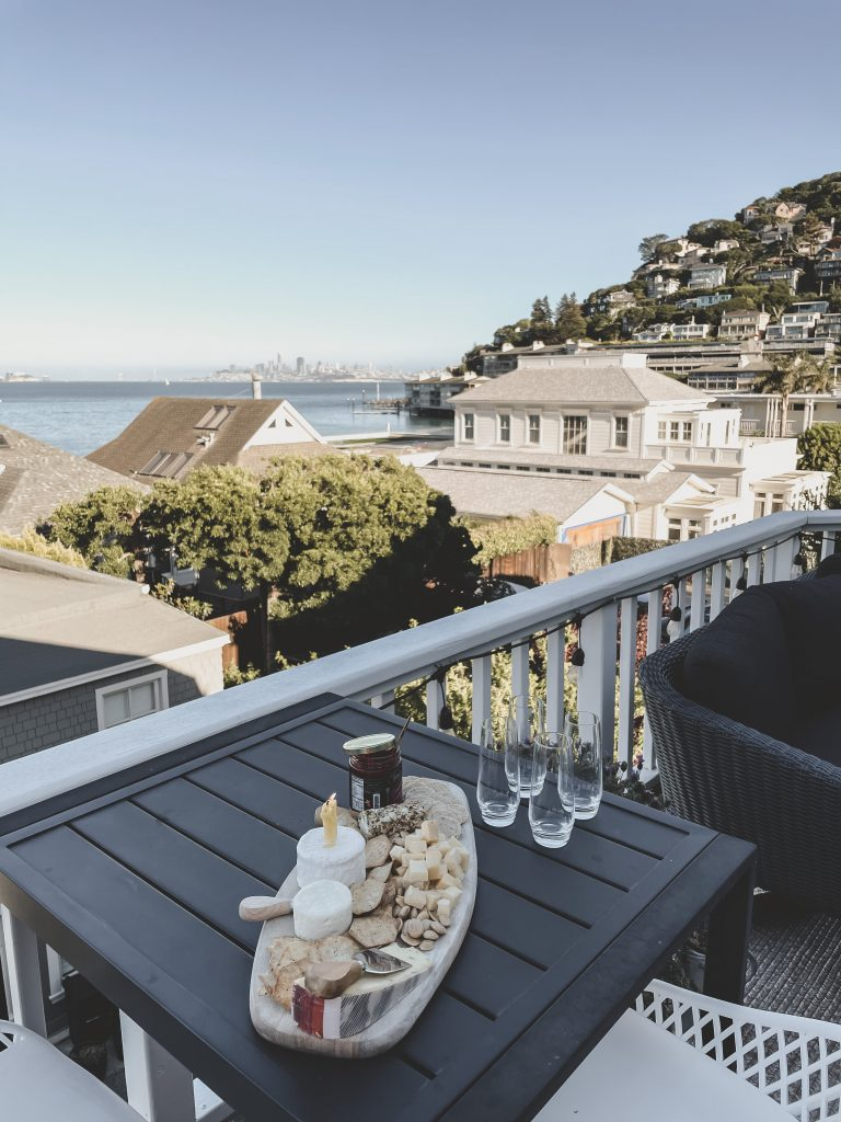 A beautiful charcuterie boar and 4 champagne flutes sit on a table on a deck overlooking the Pacific ocean.