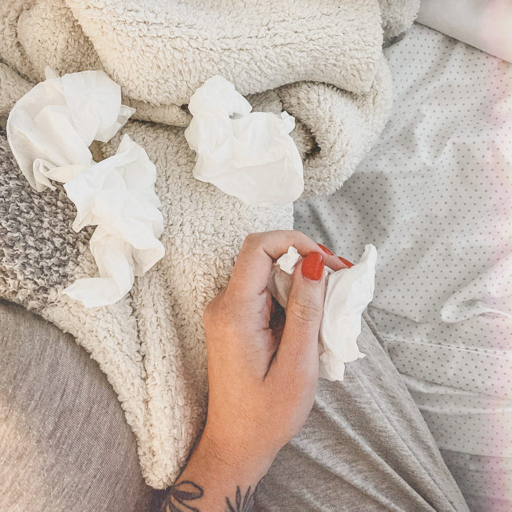 A woman's hand on a bed that's covered with tissues, with one in her hand.