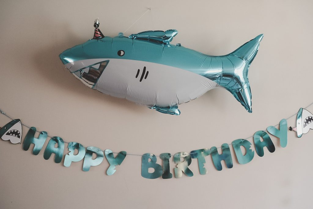 A balloon shark with a birthday hat and happy birthday banner.