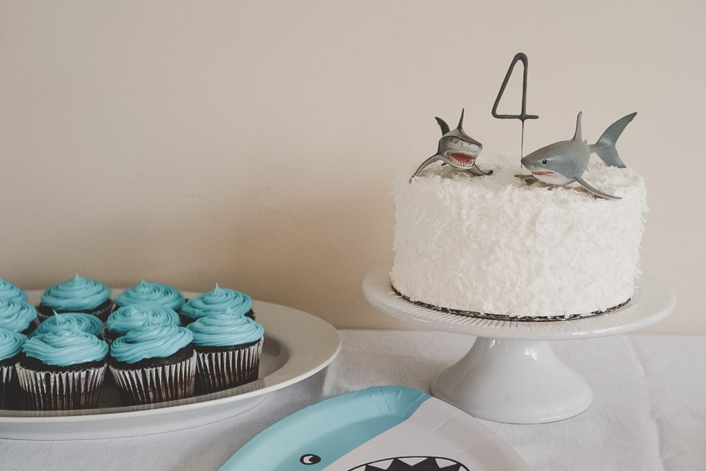 A closeup of birthday cakes with blue frosting and a coconut cake with two shark toys and a 4 candle on top.