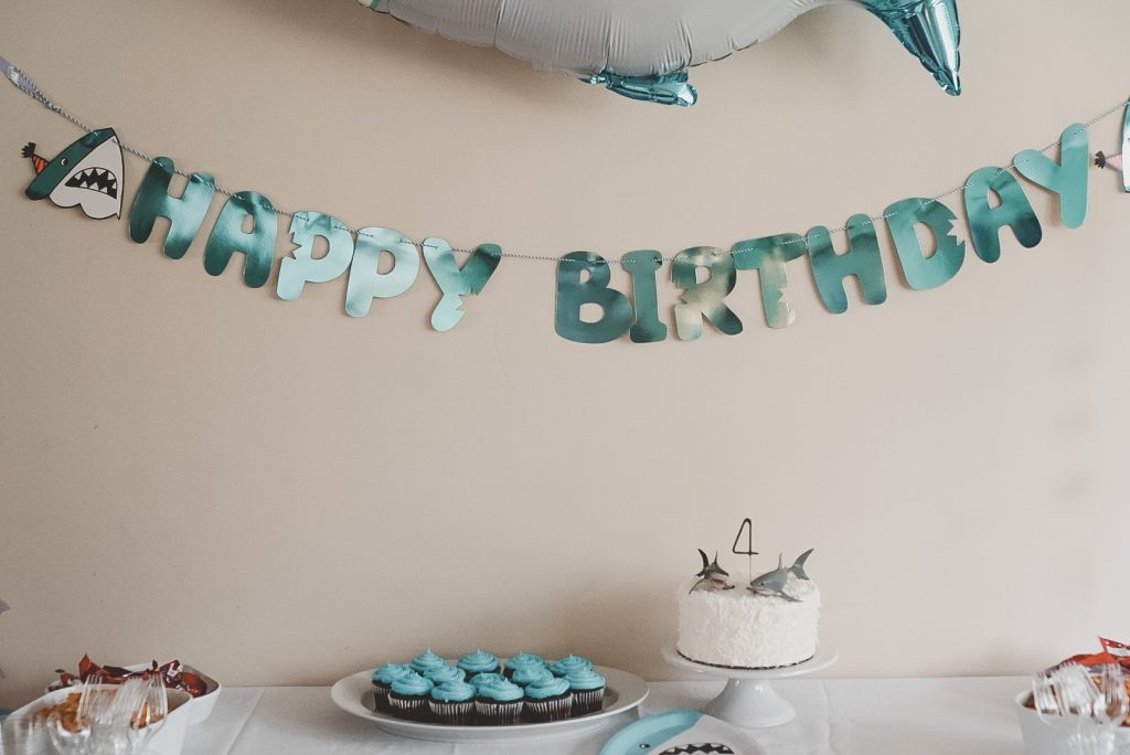 Party table at a shark-themed birthday party, shows a cake, cupcakes, and happy birthday garland.