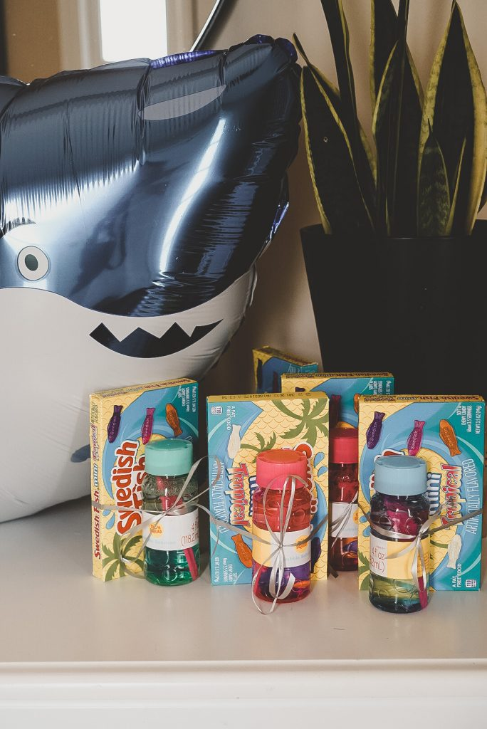 A smiling shark balloon and birthday party favors of Swedish fish and balloons.